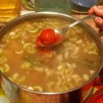 Снимаем суп с огня и кладем консервированные томаты, разминая их ложкой